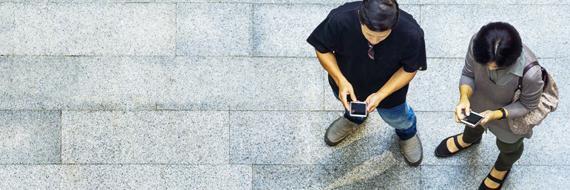 Digitale economie: twee mensen die op hun telefoon kijken.
